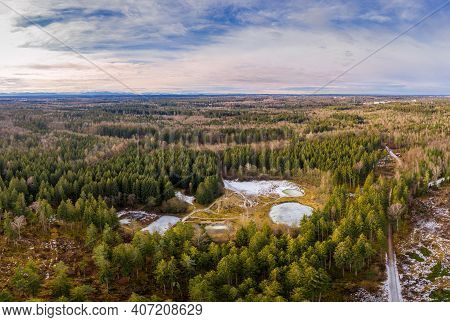 Aerial View Of A Small Lakes Inside A Forest With Conifer Trees. Idyllic Winter Moment With The Alp