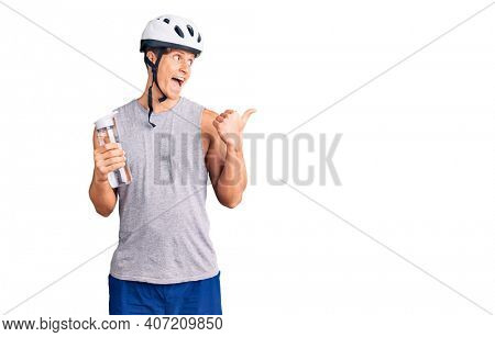 Young handsome man wearing bike helmet holding bottle of water pointing thumb up to the side smiling happy with open mouth
