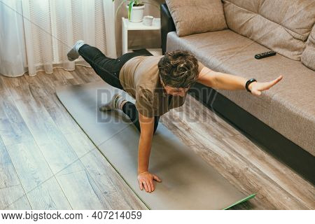 Sport In Mature Age. Happy Senior Woman Doing Stretching Exercises At Home, Watching Online Tutorial