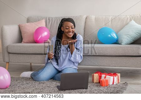 Attractive African American Young Lady With Glass Of Champagne Sending Fly Kiss While Having Online