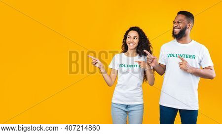 Look Aside. Two Multiethnic Volunteers Pointing Fingers At Free Space For Your Text Posing Standing