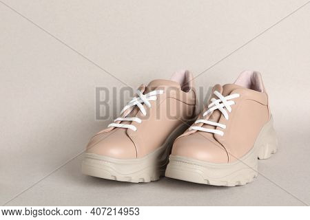 Pair Of Stylish Shoes With White Laces On Beige Background