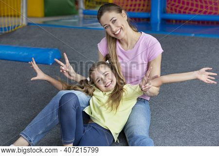 Cheerful Young Mother And Her Teenage Daughter Being Silly, Making Peace Gesture At Indoor Kids Play