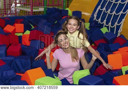 Portrait Of Young Mother And Her Teen Daughter Playing Together At Foam Ball Pool In Family Recreati