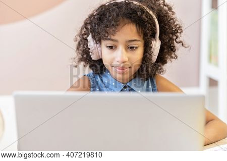 A Pretty Curly African Schoolgirl Wearing A Headphones Using A Laptop For Studying On The Distance,