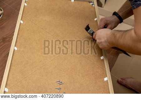 The Man Collects Furniture. A Man Collects Furniture With Hand Screwdrivers. Furniture Assembly. Mov