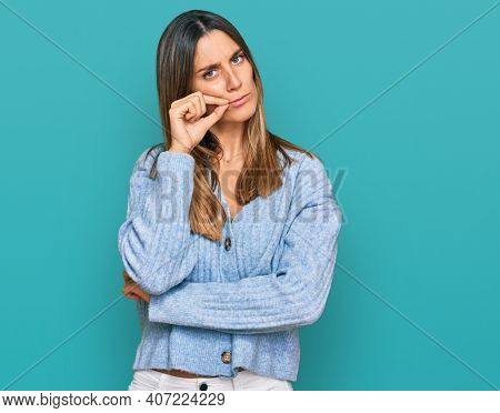 Young woman wearing casual clothes mouth and lips shut as zip with fingers. secret and silent, taboo talking