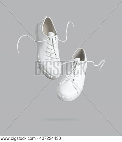 Flying White Leather Womens Sneakers Isolated On Gray Background. Fashionable Stylish Sports Casual