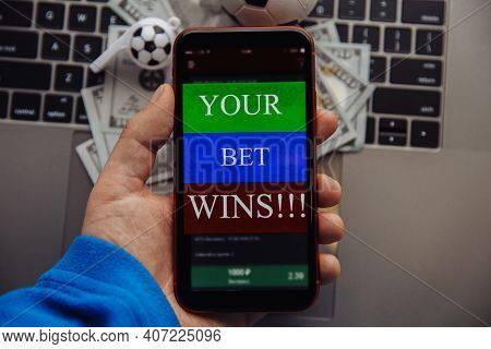 Lucky Winner At Football Betting With Phone In Hand. Dollar Bills And Soccer Ball On A Keyboard. Bet