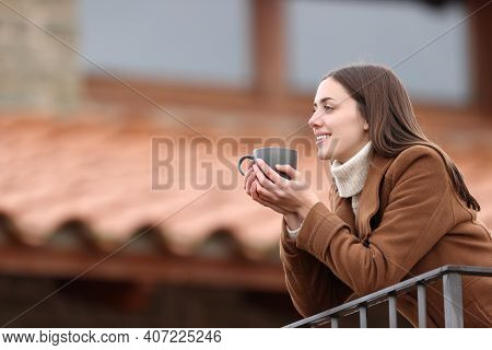 Happy Woman Contemplating Views And Drinking Coffee In A Balcony At Home In Winter