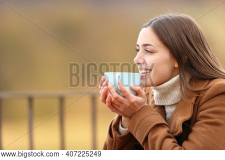 Happy Woman Drinking Coffee Contemplating Views In A Terrace In Winter In The Mountain