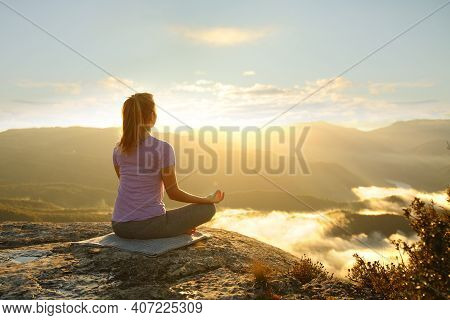 Woman Meditating Practicing Yoga Exercise In The Mountain At Sunset