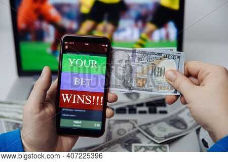 Smartphone With Betting Mobile Application And Laptop With Online Football Broadcast Behind. Bet Win