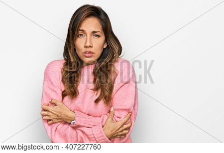 Young hispanic woman wearing casual clothes shaking and freezing for winter cold with sad and shock expression on face