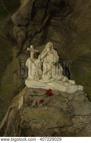 Lourdes, France, June 24, 2019: Statue Of Saint Mary Magdalene Near Calvary With The Way Of The Cros