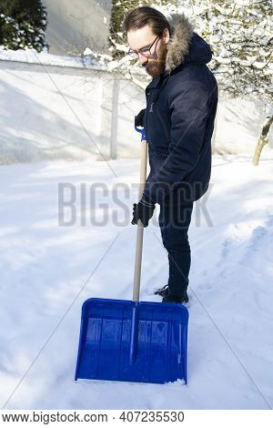 Man Shoveling Snow From A Driveway With A Snow Shovel.