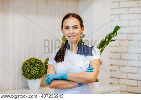 Portrait Of Young Attractive Brunette Female Doctor In Blue Medical Gloves And Uniform Posing In Whi