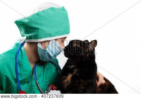 Girl In Green Medical Surgical Suit And Protective Medical Mask Plays Veterinarian With Domestic Bla