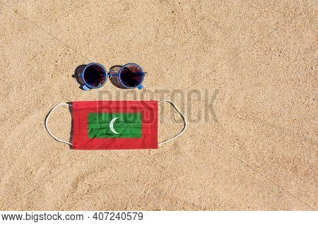 A Medical Mask In The Color Of The Maldives Flag Lies On The Sandy Beach Next To The Glasses. The Co
