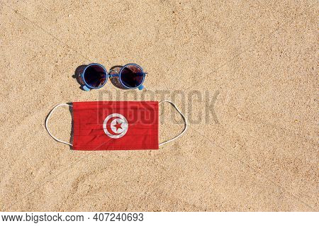 A Medical Mask In The Color Of The Tunisia Flag Lies On The Sandy Beach Next To The Glasses. The Con