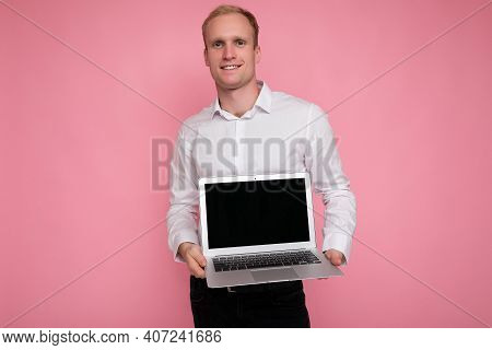 Photo Shot Of Handsome Blonde Man Holding Computer Laptop With Empty Monitor Screen With Mock Up And