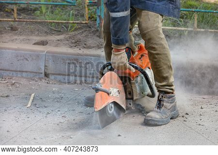 A Worker Uses A Portable Petrol Saw And A Diamond Cutting Blade To Cut Old Asphalt In A Cloud Of Dus