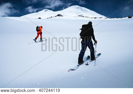Two Freeride Skiers Climb Up The Fresh Snow In A Ski Tour. The Summit Of Mount Elbrus And The Blue S