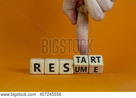 Resume And Restart Symbol. Businessman Hand Turns Cubes And Changes The Word 'resume' To 'restart'.