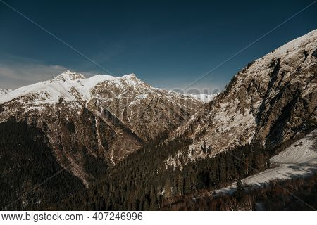 Snowy Rocky Peaks Of Mountains In Sunny Weather. Dombai Mountains Close Up.