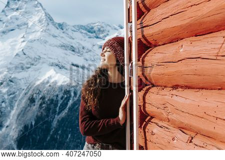 The Girl In The Snowy Mountains Is Resting In Sunny Weather. Sunburn In The Mountains In Winter.