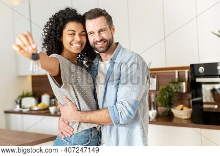 Young Interracial Married Couple Homeowners Smiling, Showing Keys From A New Apartment, Hugging And