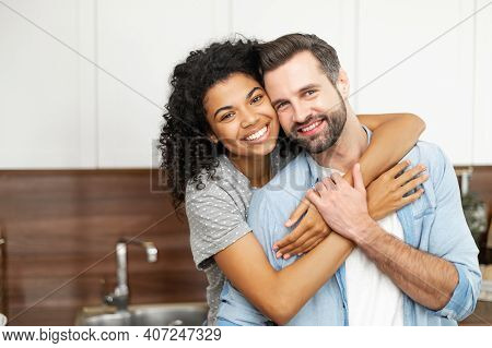 Close-up Of Happy Interracial Couple Posing Over Blurred Kitchen Background, Happy Owners Of New Fla