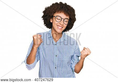 Young hispanic girl wearing business shirt and glasses very happy and excited doing winner gesture with arms raised, smiling and screaming for success. celebration concept.