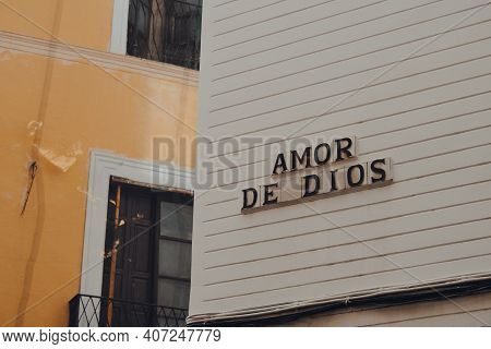 Street Name Sign On A Side Of A Wooden Building On Amor De Dios In Seville, Andalusia, Spain.
