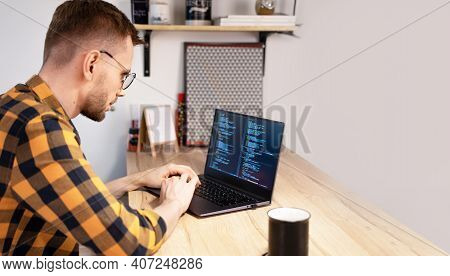 Male Programmer Using Programs Computer Code In A Bright Home. Concept Programmer Day.
