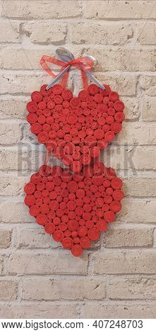 Red Hearts Hang On Brick Wall. Textured Symbol Of Love. Two Handmade Hearts On Light Brick Wall. Cop