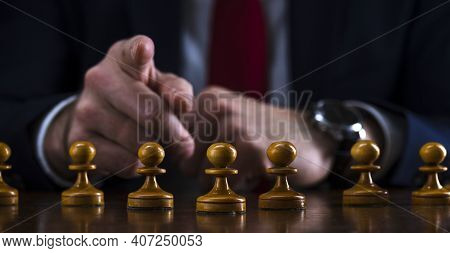 Concept Of Strategy And Business Planning, Businessman At A Chessboard In Front Of Lined Up White Pa