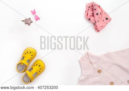 Children's Clothing And Shoes Are Laid Out On A White Background Top View. Space For The Text.