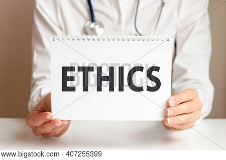 Ethics Card In Hands Of Medical Doctor. Doctor's Hands A Sheet Of Paper With Text Ethics, Medical Co