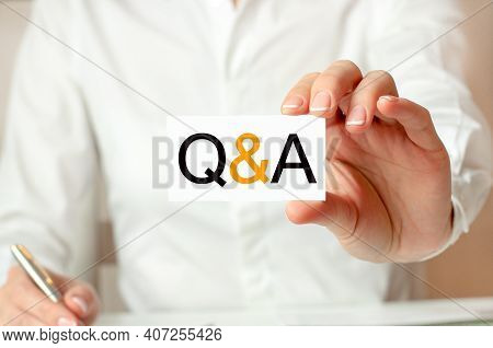 A Woman In A White Shirt Holds A Piece Of Paper With The Text: Q And A. Business Concept For Compani