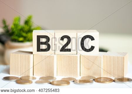 Concept Words B2c On Wooden Blocks On Beautiful Background. The Word B2c On Wood Cubes With Coins On