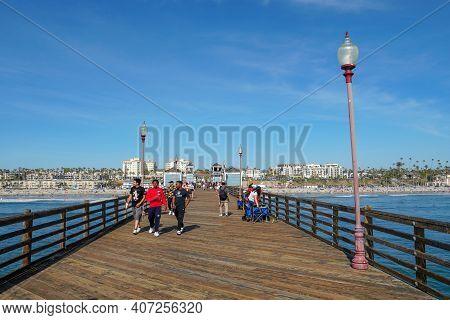 Tourist Walking On The Oceanside Pier During Blue Summer Day, Oceanside, Northern San Diego, Califor