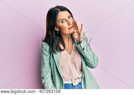 Middle age brunette woman wearing casual clothes hand on mouth telling secret rumor, whispering malicious talk conversation
