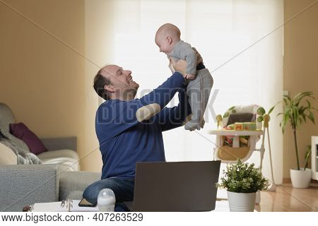 Young Father Working From Home With His Laptop And Mobile While Taking Care Of His Baby. Global Pand