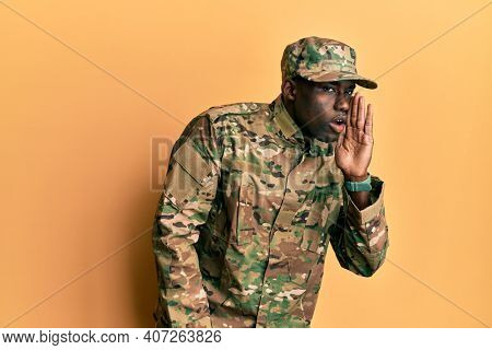 Young african american man wearing army uniform hand on mouth telling secret rumor, whispering malicious talk conversation
