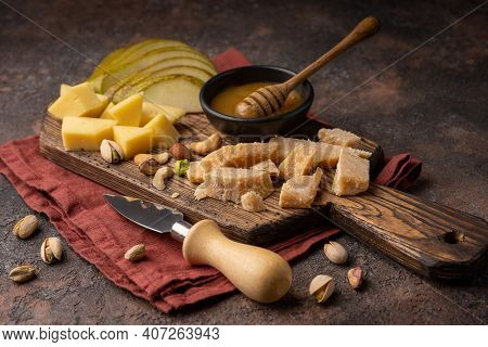 Cheese Platter With Different Cheeses, Sliced Pear, Nuts, Honey On Rustic Wooden Background. Retro S
