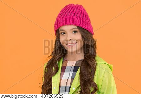 Winter Hat Styles. Kid Girl Wear Knitted Hat. Winter Accessory Concept. Girl Long Hair Yellow Backgr