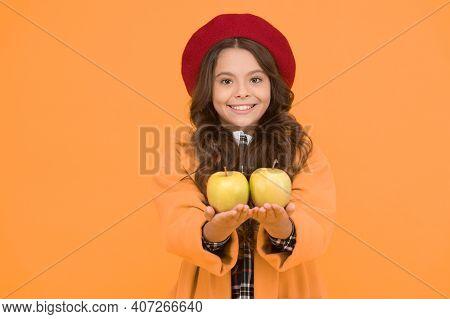 Get Vitamin Start To School Year. Happy Girl Hold Vitamin Fruit Yellow Background. Little Child Smil