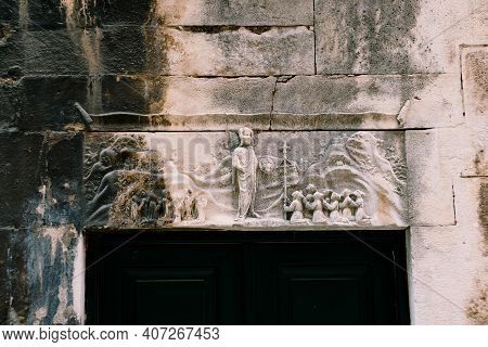 A Bas-relief Carved In Stone On The Wall Above The Black Door.
