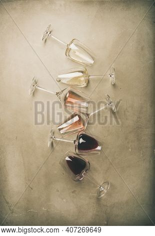 Flat-lay Of Red, Rose And White Wine In Glasses Over Grey Concrete Background, Top View, Vertical Co